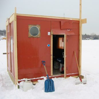 a shovel leans against a square red shanty with an open door on a snowy lake