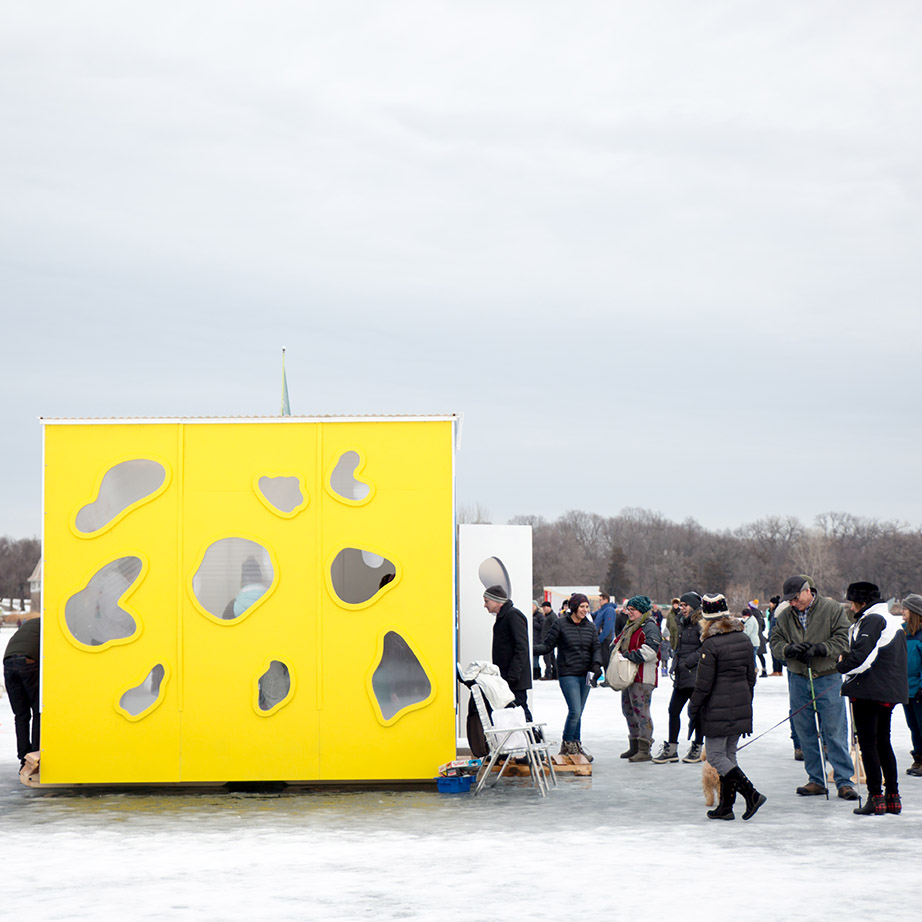 People stand on the frozen ice outside of a yellow shanty with windows shaped like lakes
