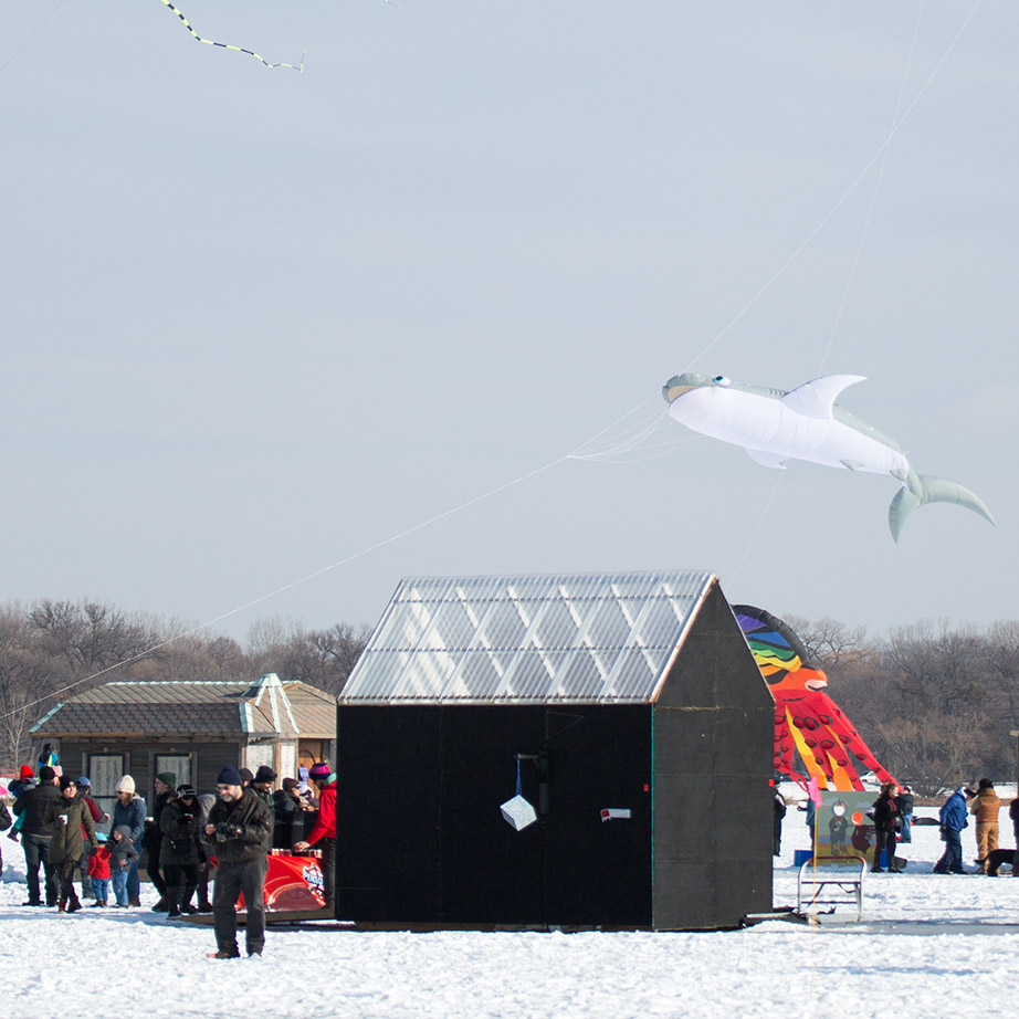 Black shanty on a frozen lake with shark-shaped kite flying above