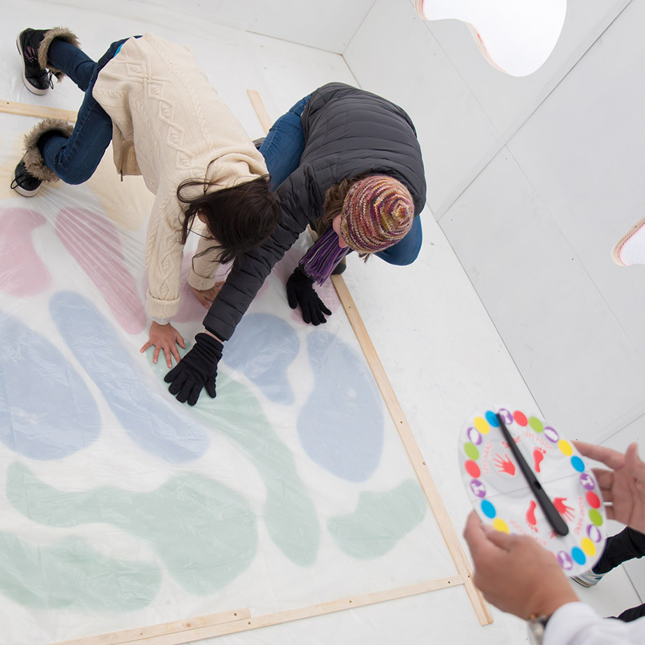 2 people crouched down playing the game twister, touching lake-shaped blobs, while hands hold a twister spinner.