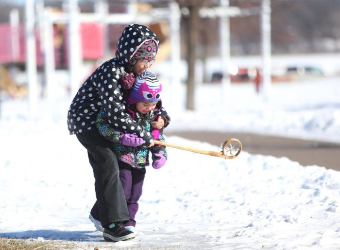 Two children on the snow with a lacrosse stick, the bigger one has their arms around the smaller one, and they both smile.