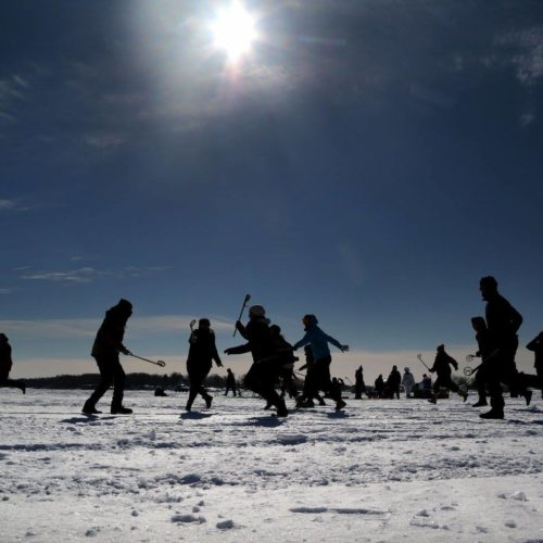 people playing lacrosse on snow-covered lake on a sunny day