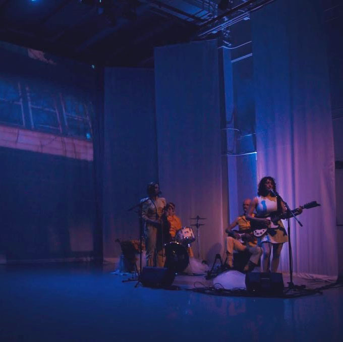 In a corner of a dimly lit theater, a band plays in pale lavender light. They look almost like mannequins in a store after hours, still, strange, and posed.