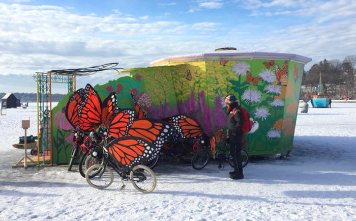 Outside the wildflower muraled Pollinator Shanty, a single person looks at the flock of monarch winged art bikes. The sky is light blue, with puffy white clouds.
