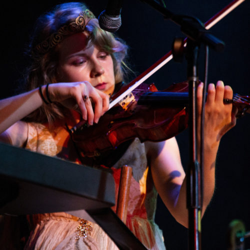 A violinist, their eyes focused on the bow, pulls it across the strings near their chin. The shadows from different lights cast warm and cool colors across their face and arms.