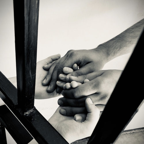 close up photo of 2 people holding hands through prison bars