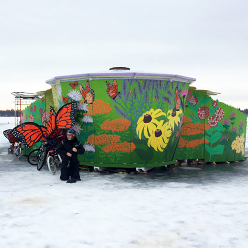 Photo of shanty painted with flowers and butterflies in the snow