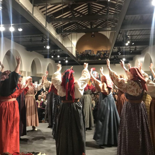 Many people in long dresses with full sleeves raise their heads up, dancing and maybe singing. They are all wearing headscarves. An audience watches from the museum's balcony above.