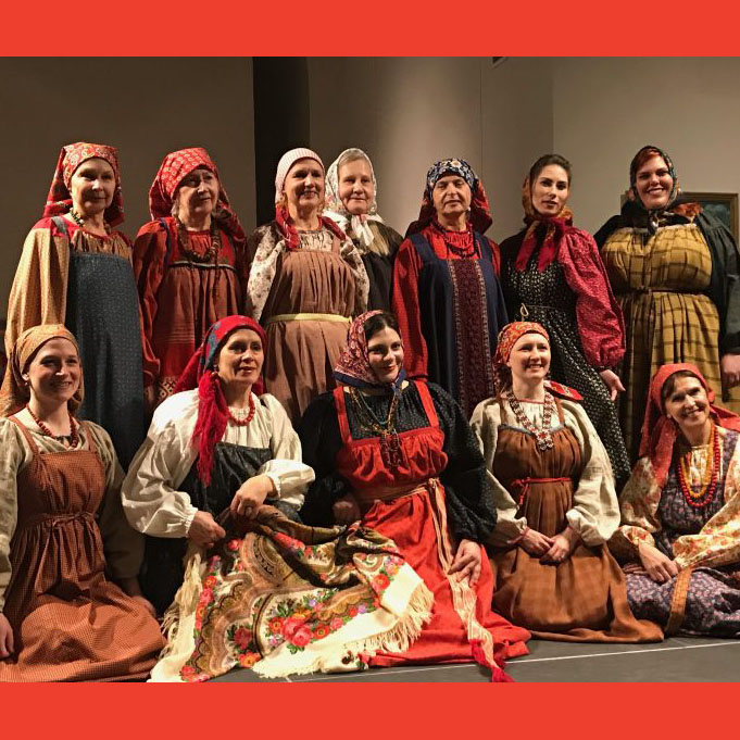 A dozen people in colorful dresses and headscarves pose for a photograph, some smiling broadly, others smile more reservedly.
