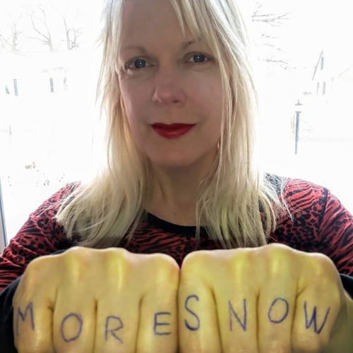 "Photo of person with ""MORE SNOW"" written on their knuckles"