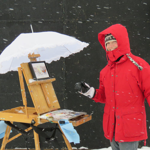 Photo of a person painting at an easel outside in the snow
