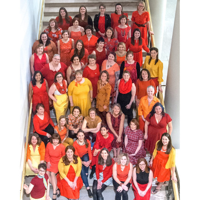 Photo of a large group of women wearing fiery colors.