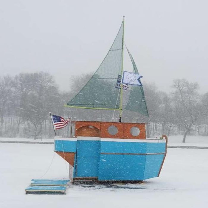 photo of a sail boat shanty in the snow on a frozen lake