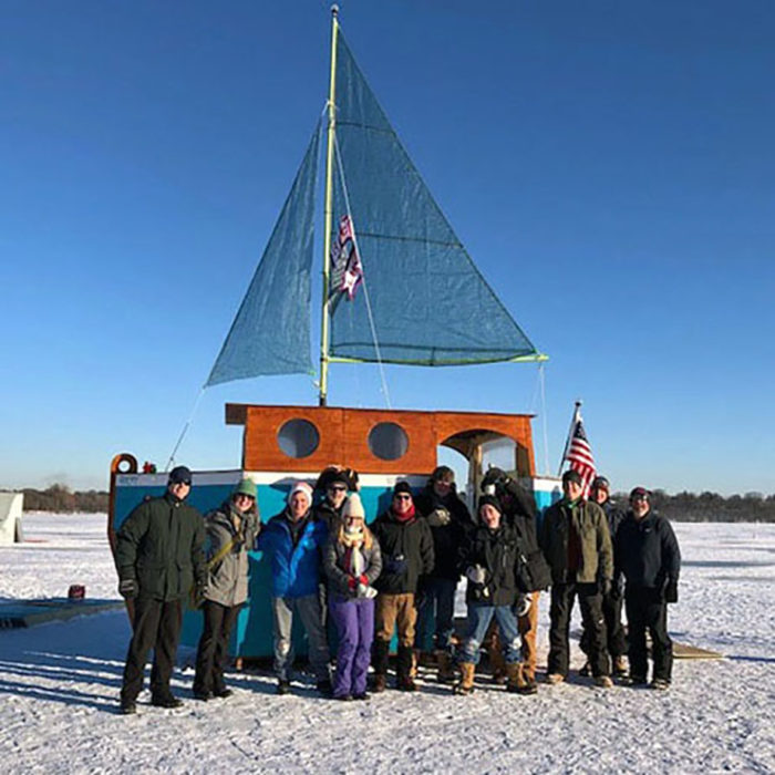 A dozen smiling people pose outside a sailboat on the ice.