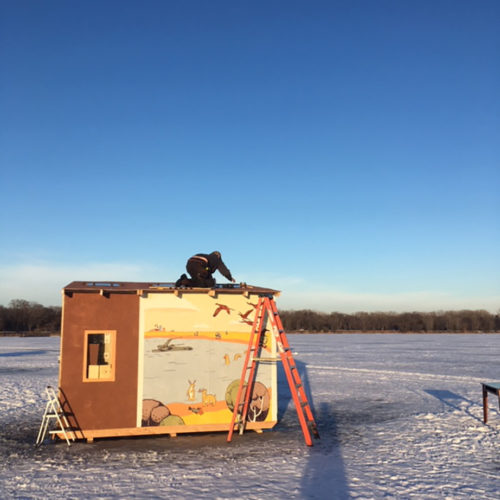 a person working on top of a shanty structure on a frozen lake