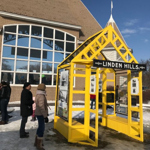 A few people stand, studying the yellow Linden Hills Neighborhood Shanty, in front of the Lake Harriet Bandshell. The yellow shanty is open and airy, and historic photographs of the neighborhood are hung on the open walls.