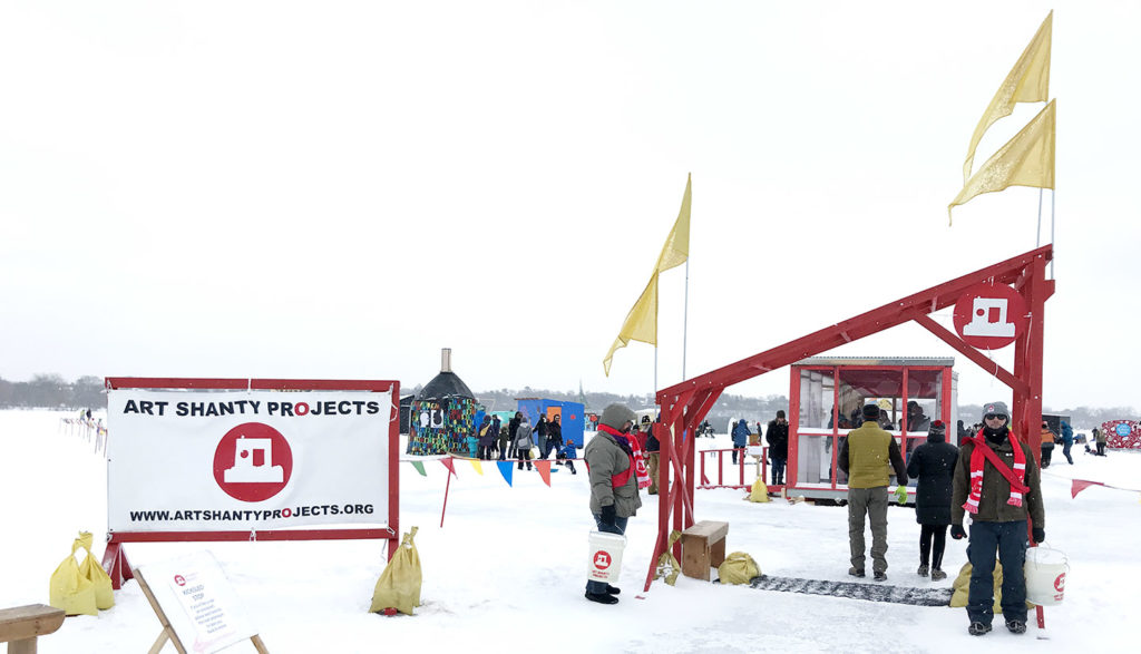Art Shanty Projects entrance gate  with flags and sign and volunteers on the frozen lake