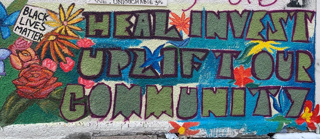 colorful painted mural on a wall with flowers and text reading: 'heal, invest, uplift our community'