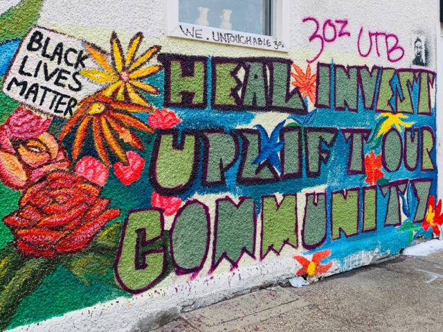 "a mural on an exterior wall with a 'black lives matter' sign, colorful flowers, and large letters reading ""heal, invest, uplift our community'"