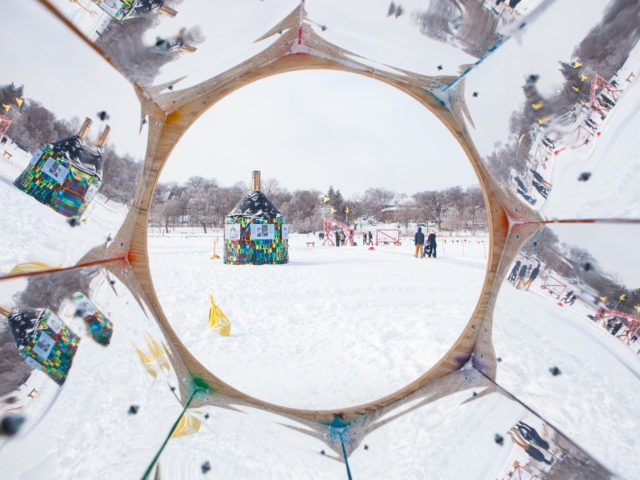 View through a mirrored kaleidoscope, with a shanty and people in the distance