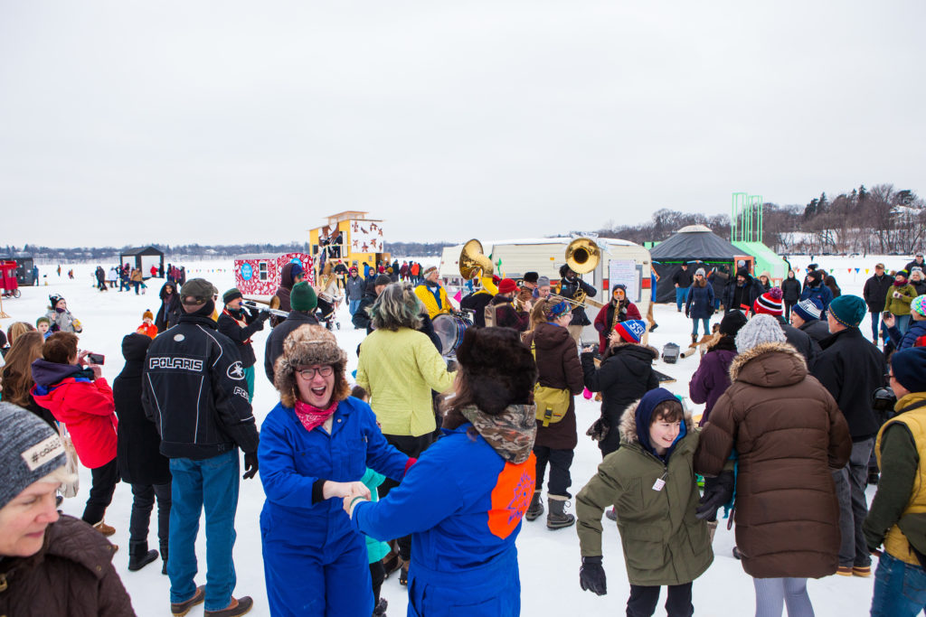 Bundled up artists and audiences joyfully dance to the tunes of Brass Messengers during a pre-pandemic day at the colorful shanty village on frozen Bde Unma in Minneapolis, February 2020.