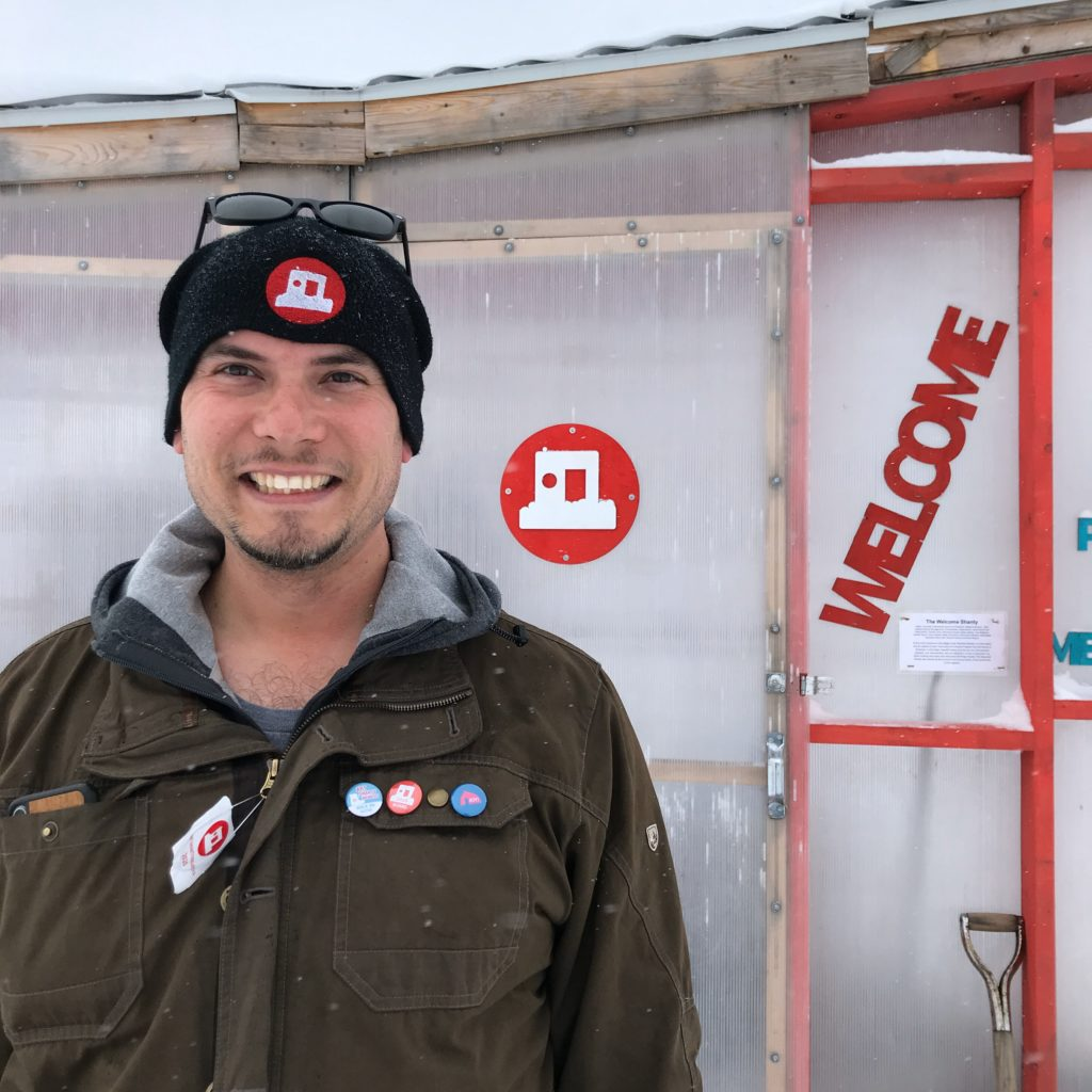 Smiling man stands in front of the Welcome Shanty with snow falling