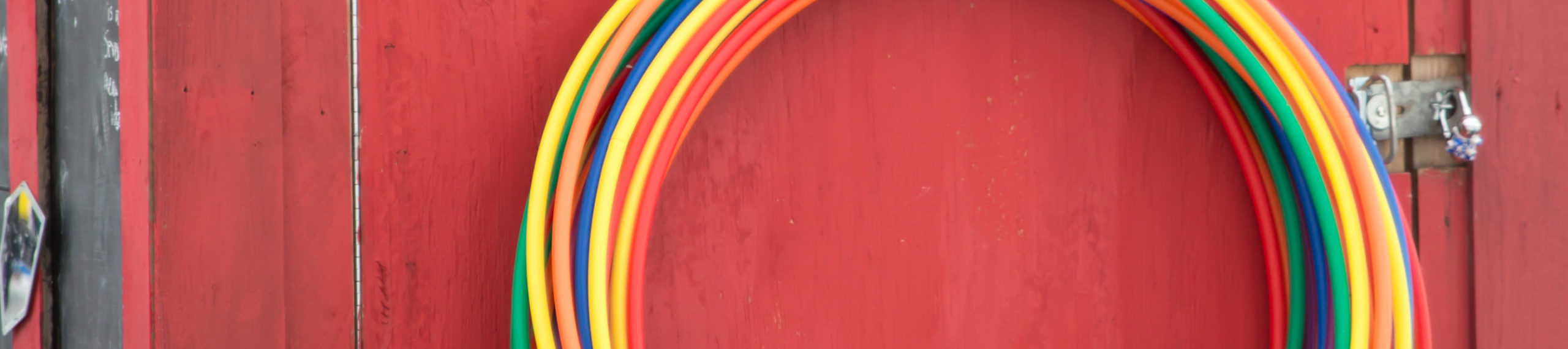 A giant pile of hula hoops in all of the colors of the rainbow lean on a red shanty door.