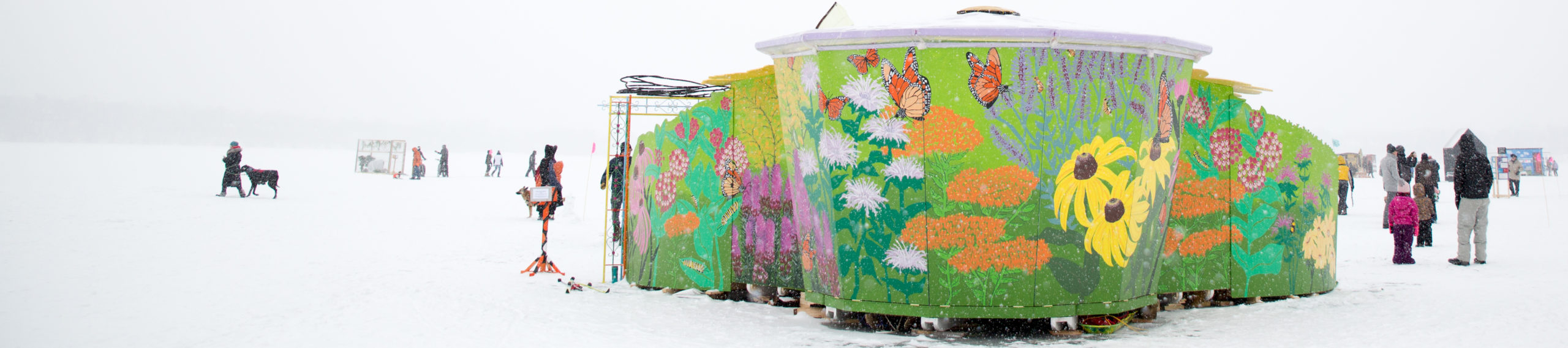 The Monarch Shanty is a bright green bowl with a white lid that disappears against the snowy sky. Painted on the structure are huge spring pollinator flowers, as big as the forms of people standing outside.