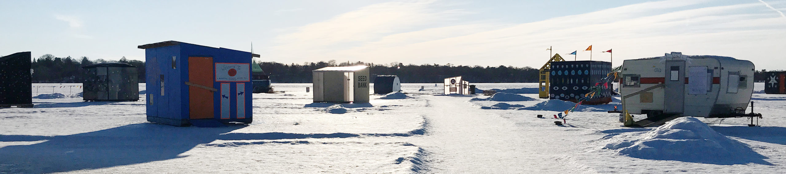 Several shanties and a small camper trailer cast long shadows onto the frozen lake. The sun reflects brightly off one roof.