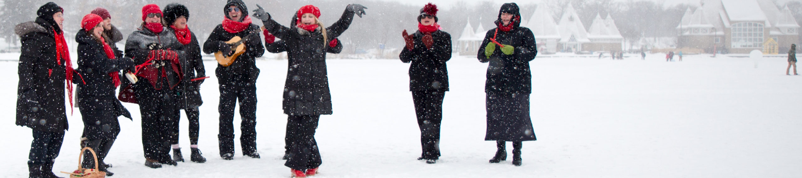A joyful person in a red beret lifts their arms and sings. They are surrounded by people with red winter accessories with small percussion instruments and a small guitar, all singing merrily.