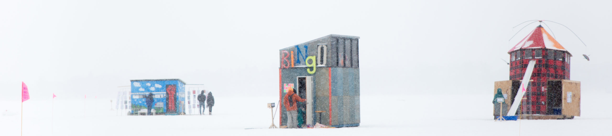 Almost pixelated by the snow, three shanties stand out against the white day: a small light blue shanty with a red door, two figures enter the bingo shanty, and a red plaid shanty that looks like a lighthouse.