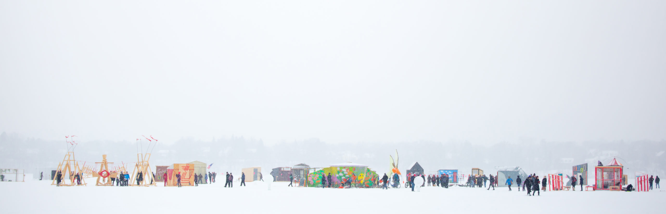 A landscape view of the Shanty Village, colorful and populated with lots of tiny figures, against the snowy grey-white sky.