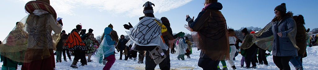 A group of adults dance in the trampled snow, in a circular formation, facing the center. Some wear butterfly wings on their bundled up bodies.