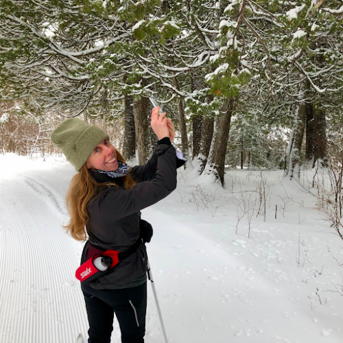 Kerri pauses and looks over her shoulder to smile for the camera against the backdrop of a snowy ski trail lined with pine trees. She is wearing cross country skis and is holding her phone to the side, interrupted briefly from taking a picture of snow on the tree boughs.