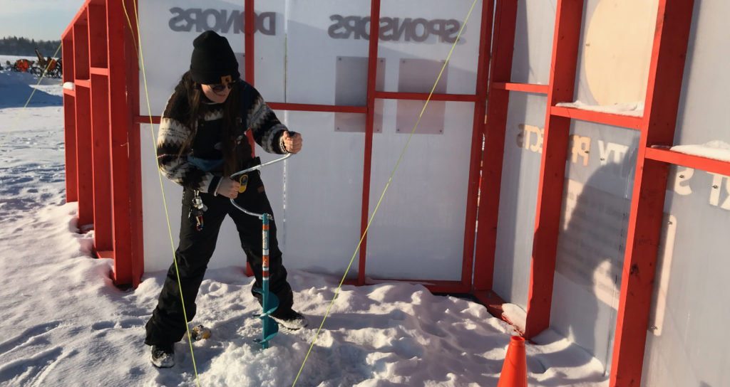 A staff member uses a hand crank auger to drill a hole in the ice behind a red and white information board on the frozen lake.