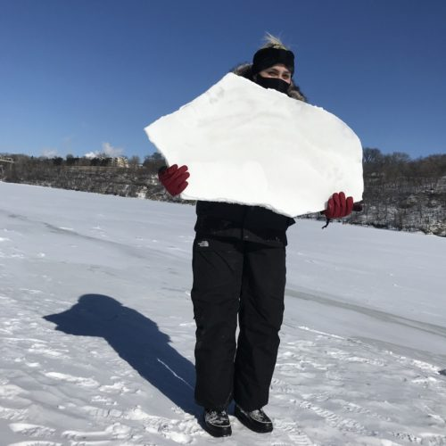 Pamela presents a gigantic sheet of snow-covered ice in front of her bundled up body, as if she just 'caught' it like a fish. She stands on a frozen river, with her long shadow extending behind her in the snow.