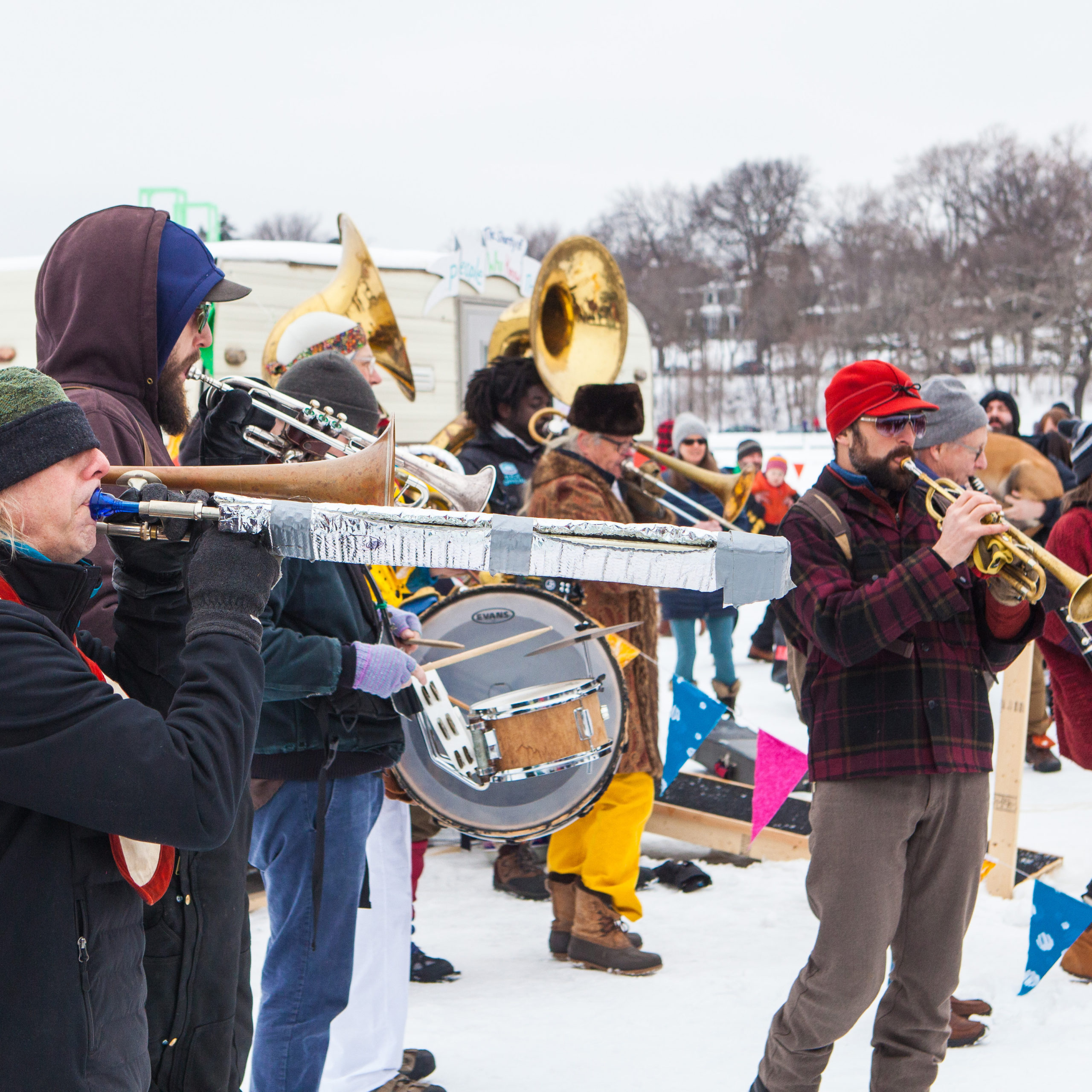A brass band plays their horns amidst a colorful village on a frozen lake.