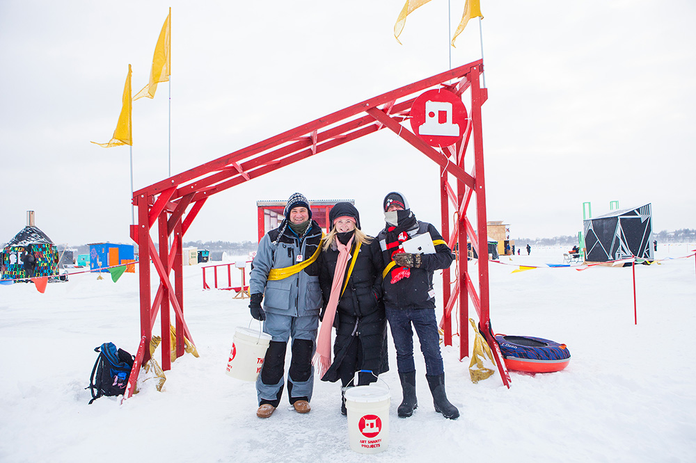 3 people in winter-wear stand in front of a red wooden gate with yellow flags on a frozen lake