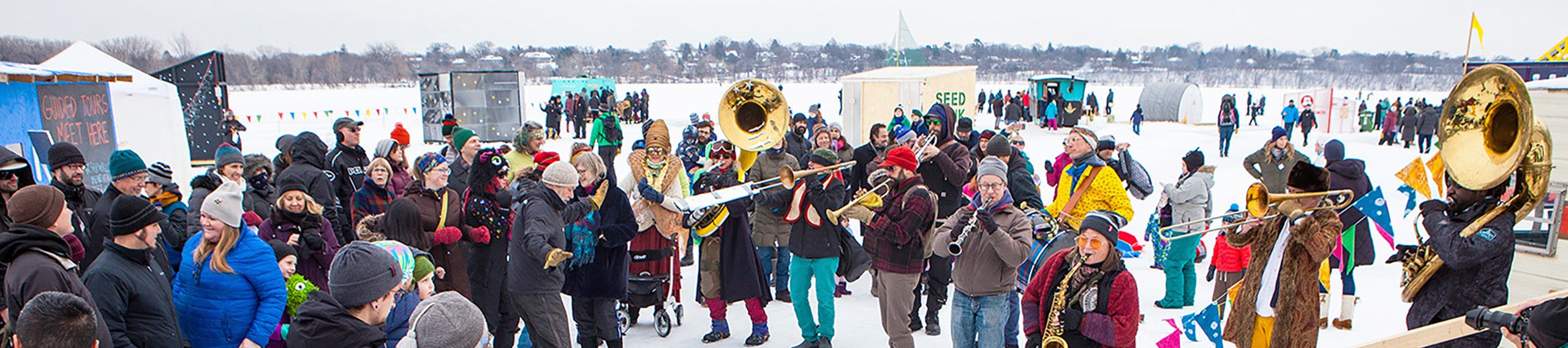 a large crowd in colorful winter-wear gathers around musicians on the frozen lake, with shanties and people in the background