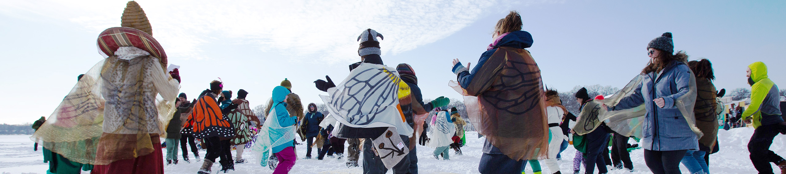 A crowd of people dance around in butterfly wings on a snow-covered lake