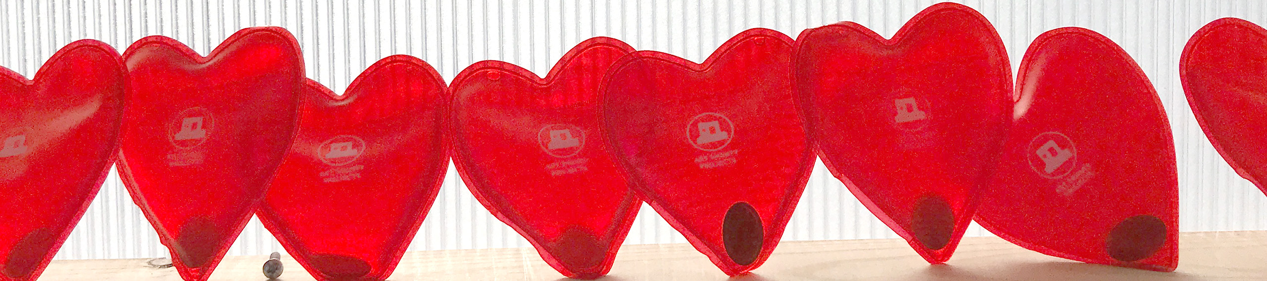 A row of red heart-shaped hand warmers with Art Shanty Projects logo on them