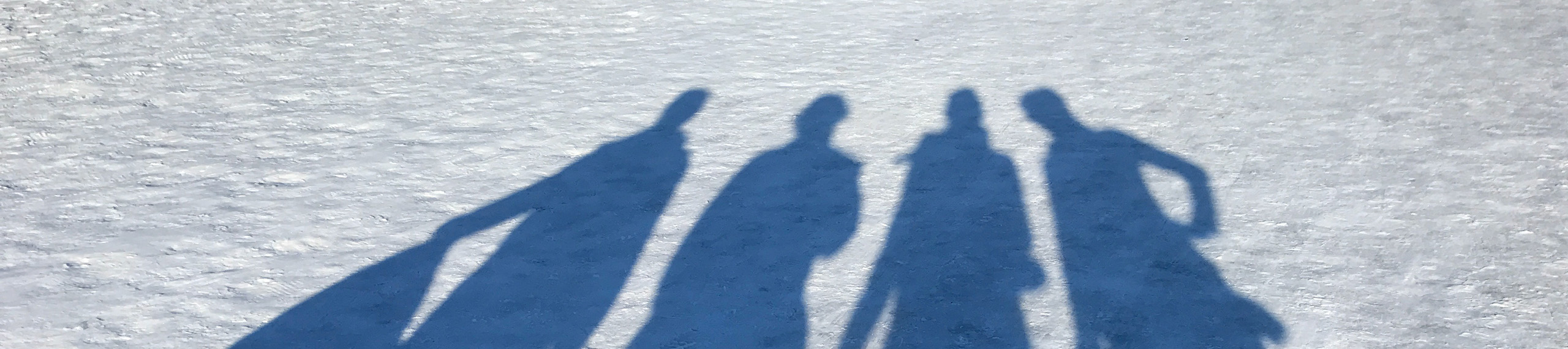 4 shadows of people stretched out against the snow